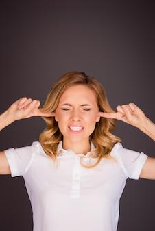 Cerrar foto de mujer joven enojada tapando los oídos con los dedos