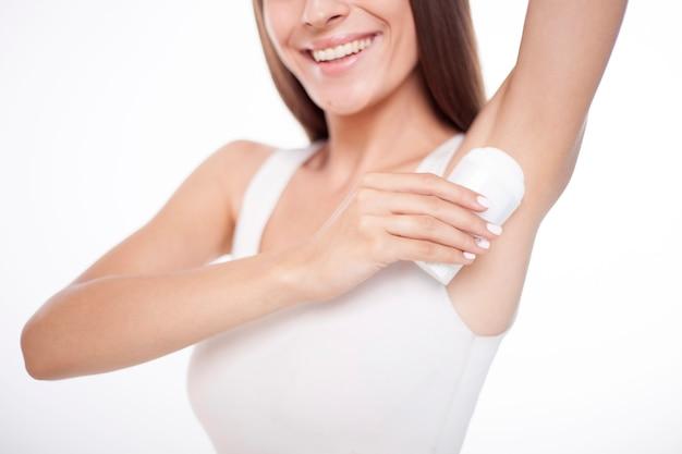 Cerrar foto de mujer joven morena está usando desodorante aislado