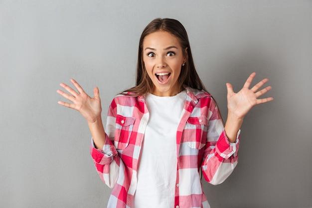 Cerrar foto de mujer morena joven sorprendida en camisa a cuadros de pie con las palmas abiertas