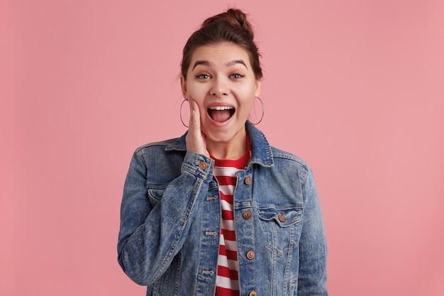 Cerrar foto de mujer con pecas, quiere contarte la impactante noticia, pone una mano a la cara, vistiendo una chaqueta de mezclilla, camiseta a rayas, mirando a la cámara, aislada sobre una pared rosa.