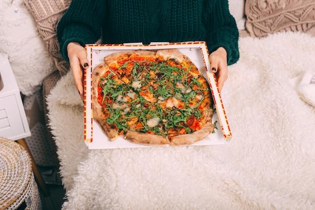 Cerrar una foto de una mujer sentada en la cama y sosteniendo una gran pizza de rúcula. concepto de pizza de entrega