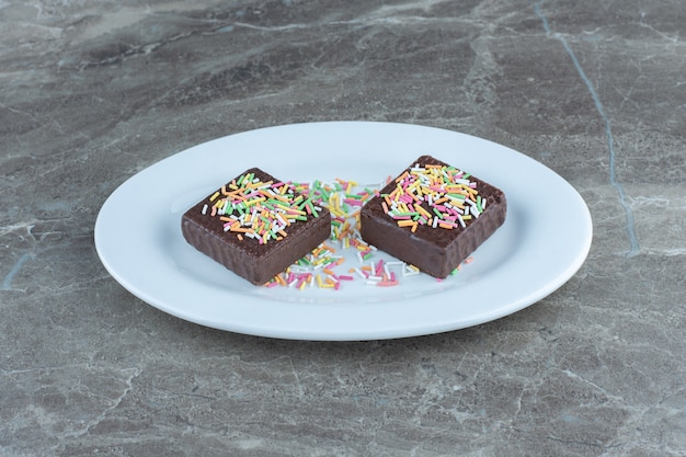 Cerrar foto de obleas de chocolate en plato de cerámica blanca.