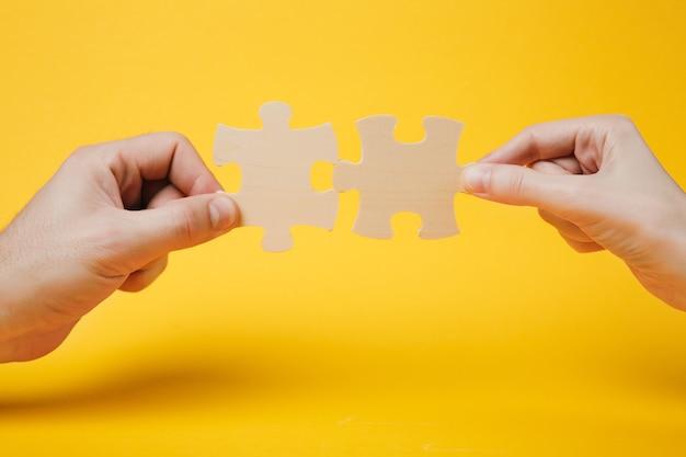 Cerrar foto recortada de manos sosteniendo tratando de conectar un par de piezas de un rompecabezas de madera aisladas sobre fondo de pared de color amarillo brillante. asociación, concepto de conexión. copie el espacio publicitario de maquetas.