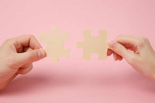 Cerrar foto recortada de manos sosteniendo tratando de conectar un par de piezas de un rompecabezas de madera aisladas sobre fondo de pared de color rosa pastel. asociación, concepto de conexión. copie el espacio publicitario de maquetas.
