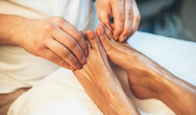 Cerrar foto de una sesión de masaje de pies realizada en un salón de spa por un masajista en las piernas del cliente