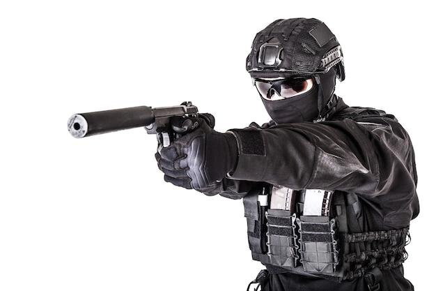 Cerrar foto del silenciador en el cañón de la pistola en manos de la policía o el combatiente de las fuerzas especiales del ejército en uniforme negro y casco, con la cara oculta detrás de la máscara, apuntando a la cámara, aislado sobre fondo blanco.