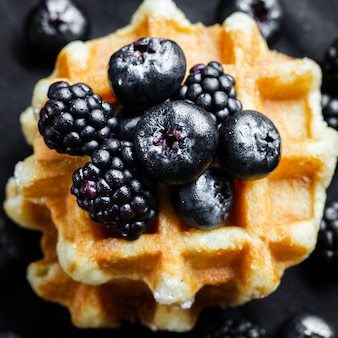 Cerrar frutas del bosque negro en waffles