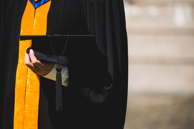 Cerrar graduado sosteniendo un sombrero. concepto de educación para el éxito en la universidad.