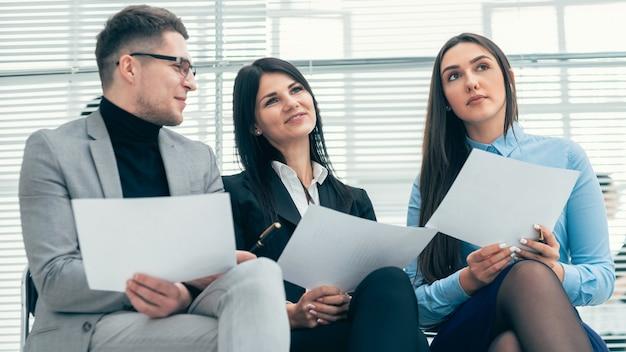 Cerrar un grupo de empleados discutiendo el cuestionario para la entrevista.