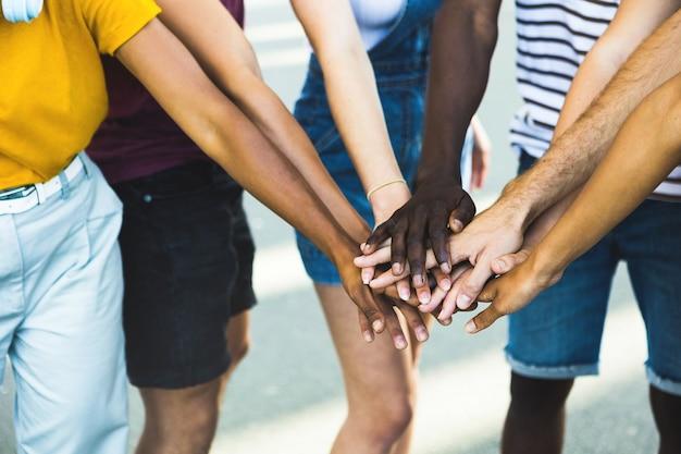 Cerrar grupo multiétnico de jóvenes estudiantes apilando las manos juntas