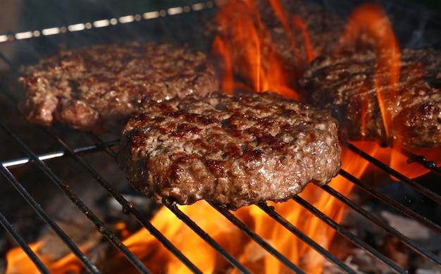 Cerrar hamburguesas de barbacoa de carne de res o cerdo para hamburguesas preparadas a la parrilla en parrilla de llama de fuego de barbacoa, vista de ángulo alto
