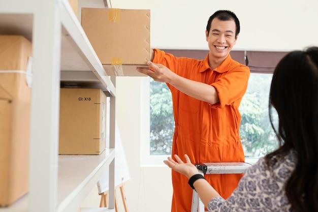 Cerrar el hombre ayudando a la mujer a llegar a la caja de entrega