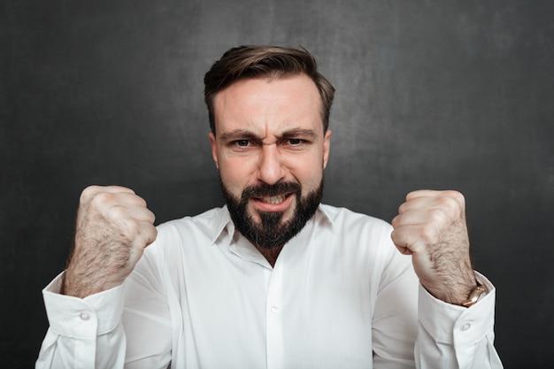 Cerrar hombre barbudo mostrando su fuerza en la cámara con los puños cerrados, aislado sobre gris oscuro