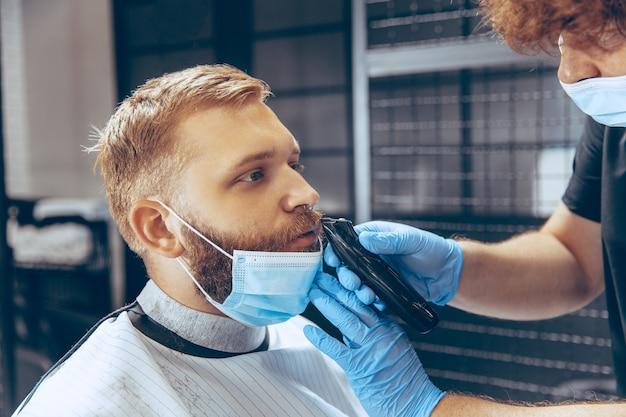 Cerrar hombre cortándose el pelo en la barbería con máscara durante la pandemia de coronavirus.