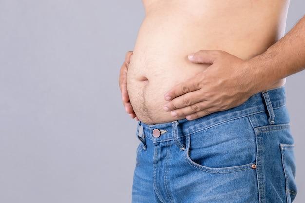 Cerrar hombre gordo de pie y mostrar su barriga con. gente gorda y concepto saludable