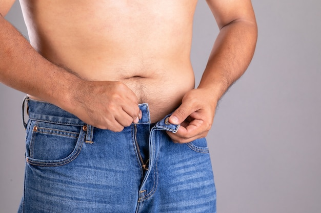 Cerrar hombre gordo tratando de abotonarse los pantalones