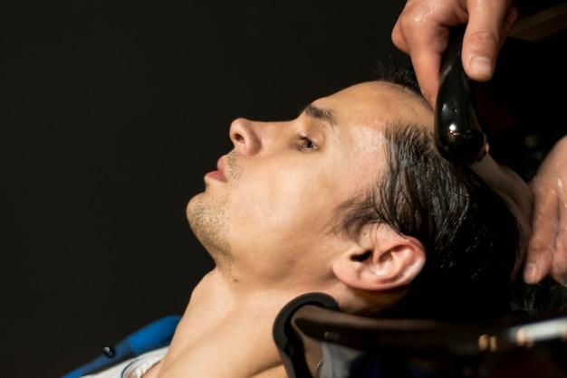 Cerrar hombre lavándose el pelo
