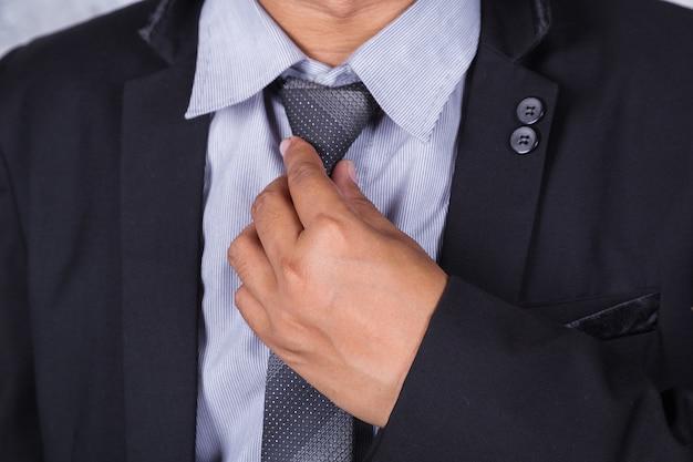 Cerrar hombre de negocios en traje arreglando su corbata