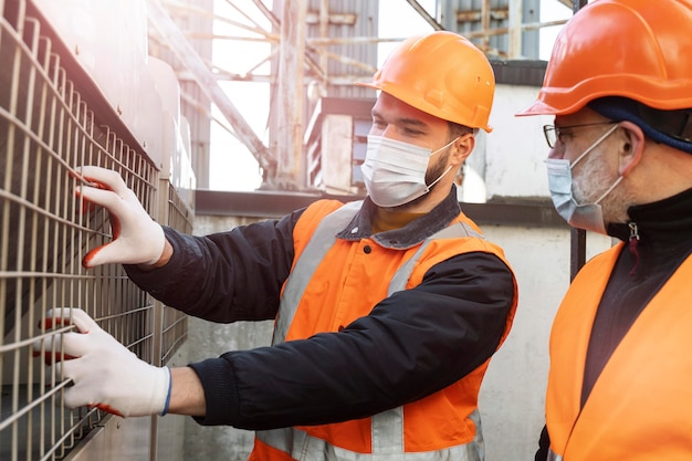 Cerrar hombres con máscaras trabajando juntos