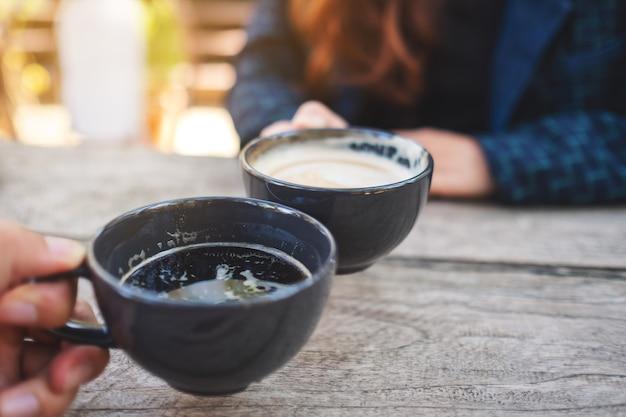 Cerrar imagen de dos personas tintineo de tazas de café en la mesa de madera