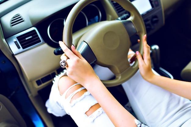 Cerrar imagen de estilo de vida de mujer elegante conduciendo su coche, manicura perfecta y accesorio, pantalones locos de mezclilla vintage, concepto de carretera de viaje.
