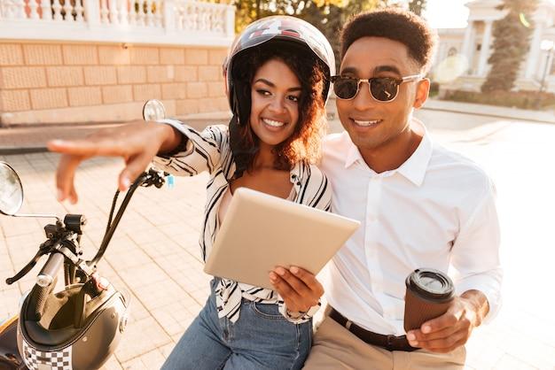 Cerrar imagen de feliz pareja africana sentada en moto moderna con tablet pc en la calle mientras la mujer apuntando lejos