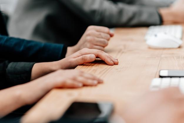Cerrar imagen de un grupo de empleados sentados en una mesa