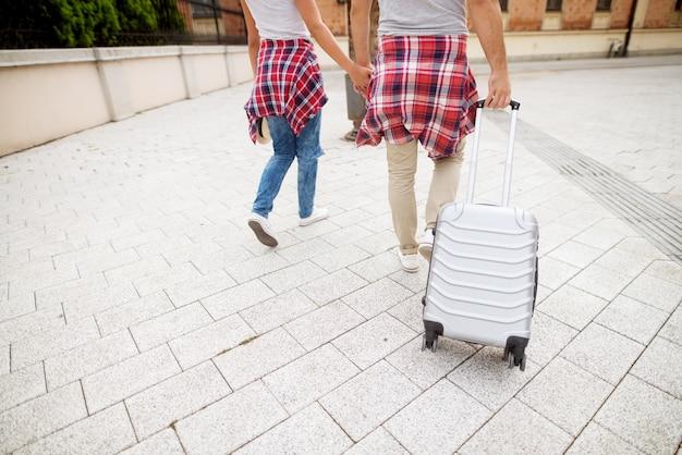Cerrar imagen de una joven pareja cariñosa caminando por la acera con una bolsa mientras cogidos de la mano.