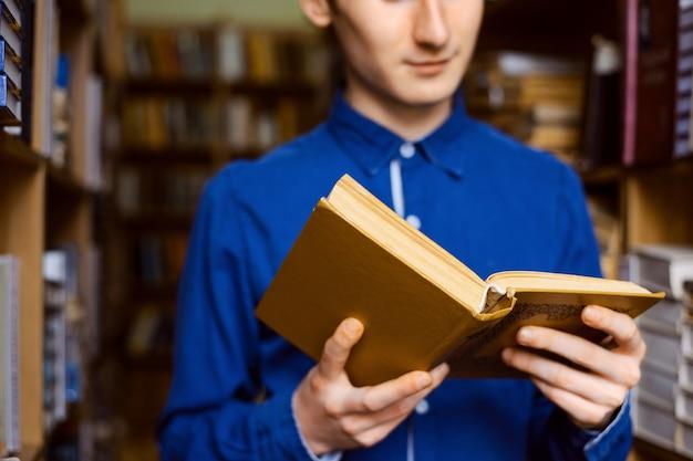 Cerrar imagen de un libro en manos del estudiante masculino de pie entre los estantes de libros en la biblioteca