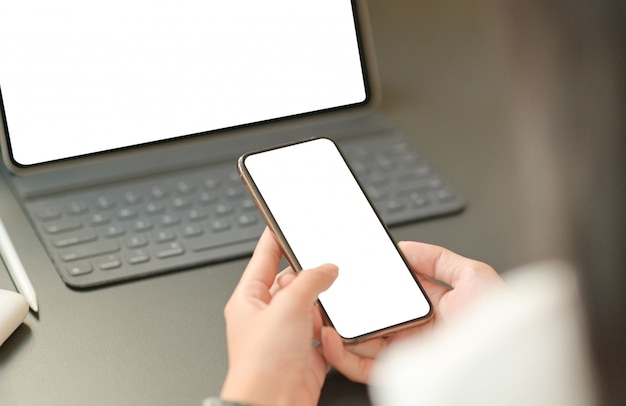 Cerrar imagen de la mano de una empresaria está utilizando un teléfono inteligente de pantalla en blanco con una computadora portátil.
