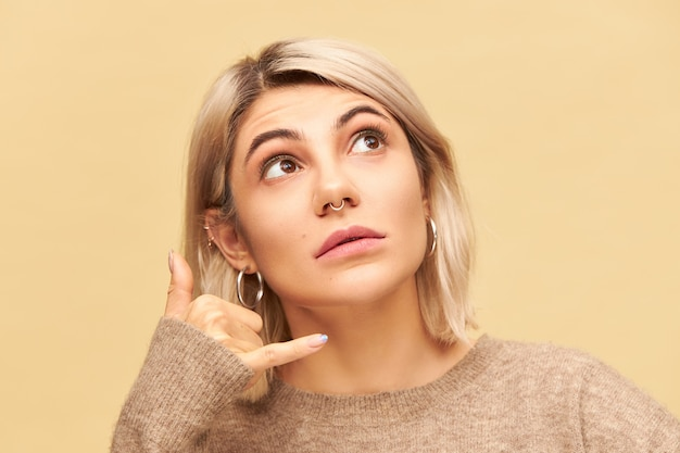Cerrar imagen de mujer bonita con peinado bob rubio y anillo en la nariz mirando hacia arriba, sosteniendo la mano en la oreja con el pulgar y el meñique extendidos ampliamente, haciendo el gesto llámame. lenguaje corporal