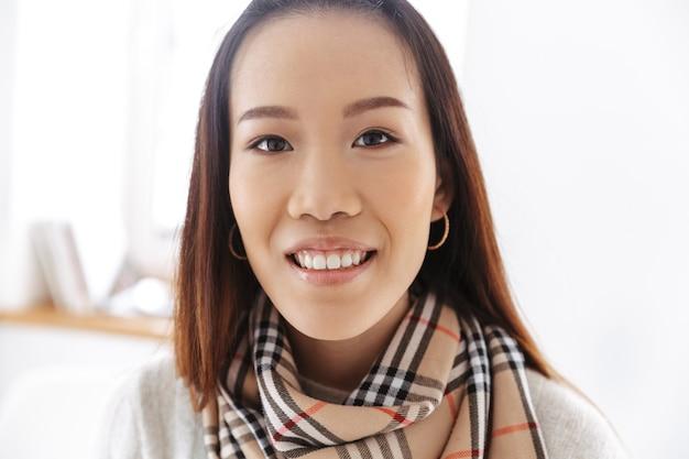 Cerrar imagen de mujer de negocios asiática sonriente mirando al frente mientras está en la oficina