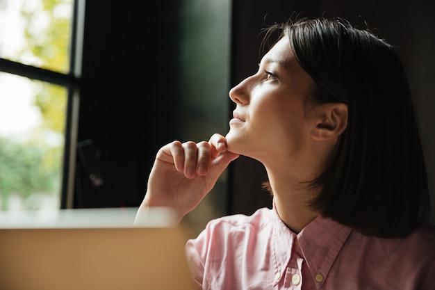 Cerrar imagen de mujer pensativa sentada junto a la mesa