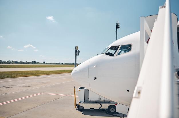 Cerrar imagen de parte del avión de pasajeros descargando equipaje al aire libre
