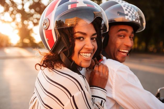 Cerrar imagen de vista lateral de la feliz pareja africana monta en moto moderna al aire libre y mirando a la cámara