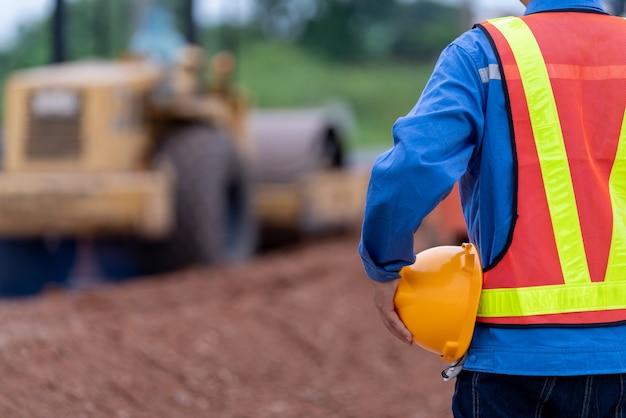 Cerrar ingeniero civil con casco en el sitio de construcción de carreteras