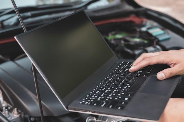 Cerrar un ingeniero mecánico que usa equipo de diagnóstico electrnoico para sintonizar un automóvil