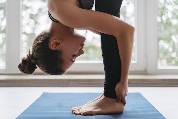 Cerrar joven mujer deportiva practicando yoga en casa o en el estudio de yoga, haciendo ejercicio de rodillas