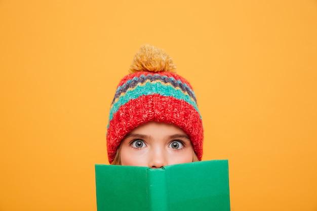 Cerrar joven sorprendida en suéter y sombrero escondiéndose detrás del libro y mirando a la cámara sobre naranja