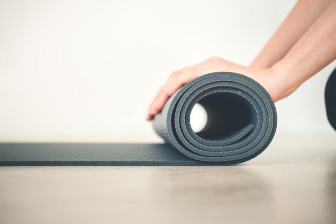 Cerrar la estera de la yoga del balanceo de la mano de la mujer en clase de la yoga resuelve