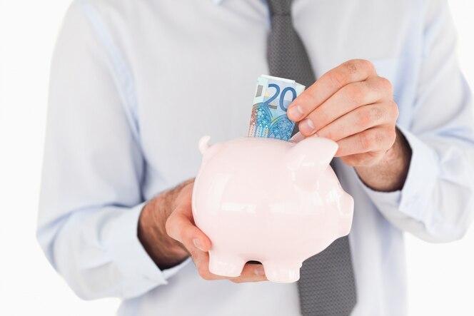 Cerrar las manos poniendo un billete de banco en una alcancía