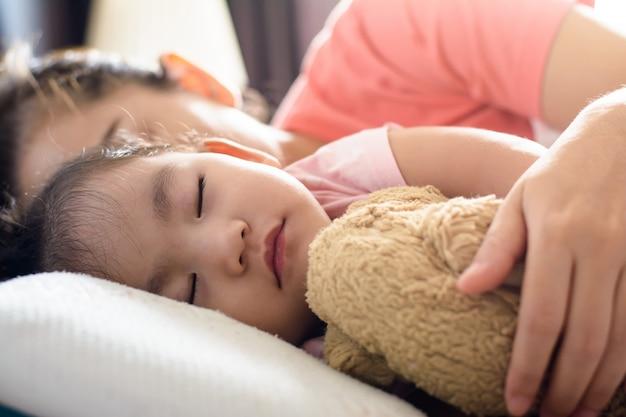 Cerrar linda niña asiática y su madre durmiendo en la cama. vista lateral