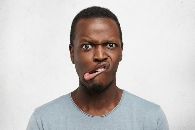Cerrar loco tonto joven africano haciendo bocas, frunciendo el ceño, mirando con mirada aterrorizada de miedo, posando en el interior en la pared gris. expresiones faciales humanas y emociones