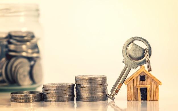 Cerrar el lugar del modelo de la casa en el apilamiento de monedas de dinero para el concepto de hipoteca y préstamo hipotecario, refinanciamiento o inversión inmobiliaria