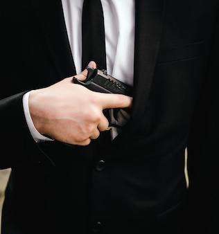 Cerrar la mano borrosa con una pistola de hombre con traje, chaqueta y camisa blanca, corbata negra.