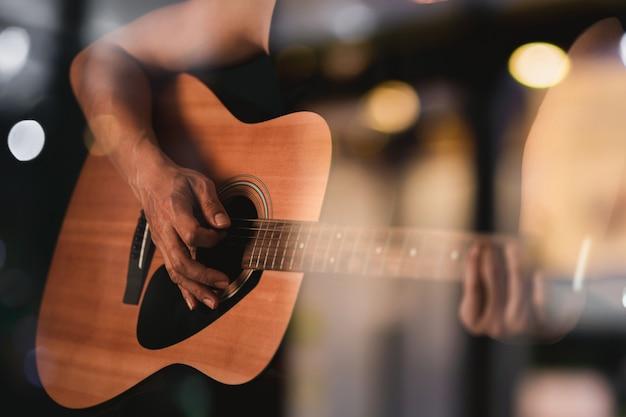 Cerrar la mano del chico tocando la guitarra