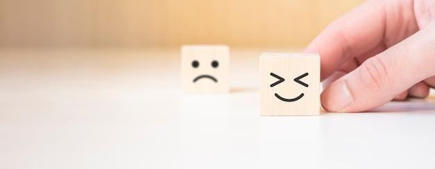 Cerrar la mano del cliente elija la cara sonriente y el icono de la cara triste borrosa en el cubo de madera, calificación del servicio, concepto de satisfacción.
