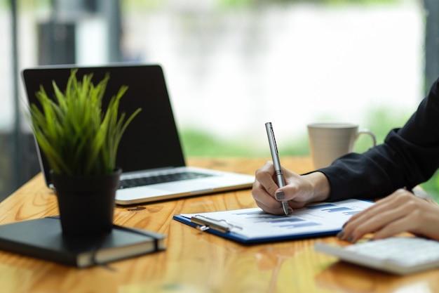 Cerrar la mano dama de negocios firmando un documento financiero haciendo un contrato comercial