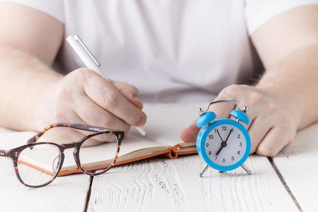 Cerrar la mano del estudiante escribiendo notas en el cuaderno