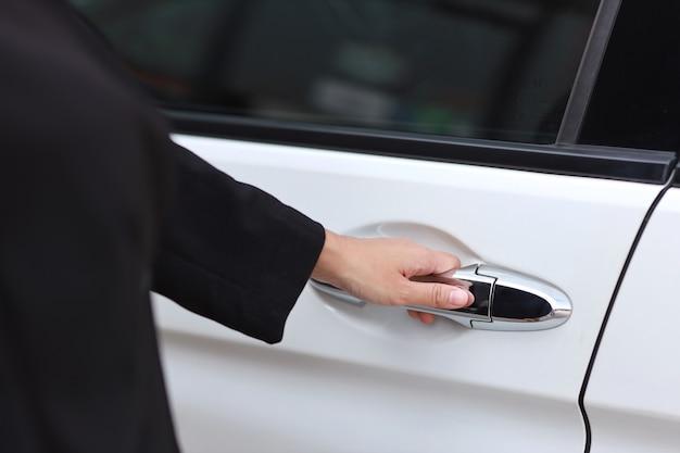 Cerrar la mano femenina abriendo la puerta del automóvil o automóvil